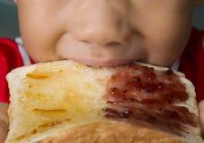 O menino asiático morde o pão branco com doce de morango do doce de fruta alaranjado Imagens de Stock Royalty Free