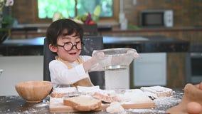 O menino asiático pequeno bonito que peneira a farinha da massa com o escorredor da peneira da peneira na cozinha da casa para pr filme