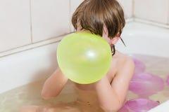 O menino banha-se em um banheiro com balões foto de stock royalty free