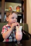 O menino bebe o milkshake Fotografia de Stock