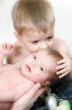 O menino beija sua irmã recém-nascida imagem de stock royalty free