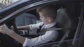 O menino bem vestido novo que aprende conduzir o carro que senta-se no close-up do assento de motoristas Mi?do moderno O menino n filme