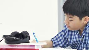 O menino bonito asiático que faz seus trabalhos de casa com cara do sorriso em casa, a zorra 4K disparou video estoque