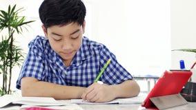 O menino bonito asiático que faz seus trabalhos de casa com cara do sorriso em casa, a zorra 4K disparou vídeos de arquivo