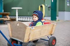 O menino bonito da criança de dois anos no trole de madeira no outono veste-se Imagem de Stock Royalty Free