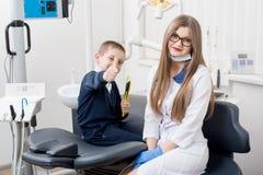 O menino bonito da criança que sorri na cadeira do ` s do dentista e que mostra manuseia acima dos gestos da boa classe imagem de stock