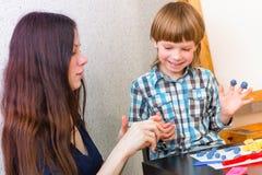O menino bonito e sua mãe jogam a jogo-massa colorida junto Passatempo na família feliz fotos de stock