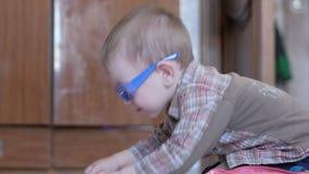 O menino bonito em vidros engraçados tira com ambas as mãos no papel em casa vídeos de arquivo