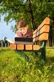 O menino bonito está encontrando-se em um banco no parque, olhando a tabuleta Imagem de Stock