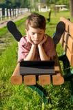 O menino bonito está encontrando-se em um banco no parque, olhando a tabuleta Foto de Stock