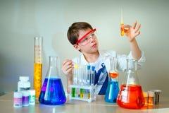 O menino bonito está fazendo experiências da ciência em um laboratório Imagens de Stock Royalty Free