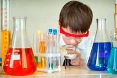 O menino bonito está fazendo experiências da ciência em um laboratório Fotos de Stock