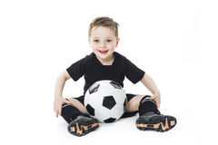 O menino bonito está mantendo uma bola do futebol isolada no fundo branco Futebol Foto de Stock
