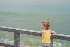 O menino bonito está na costa que olha as ondas de oceano imagem de stock
