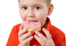 O menino bonito feliz pequeno está comendo a filhós na parede branca do fundo A criança está tendo o divertimento com filhós Alim imagens de stock