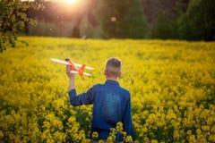 O menino bonito guarda o plano do brinquedo em sua m?o no por do sol no dia de ver?o Vista traseira fotos de stock