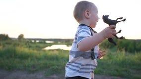O menino bonito guarda um brinquedo pequeno do cavalo e corre-o felizmente com ele na estrada no por do sol vídeos de arquivo