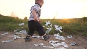 O menino bonito joga felizmente uma pilha enorme de notas de dólar para a terra, movimento lento vídeos de arquivo