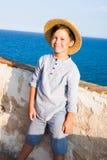 O menino bonito no chapéu de palha sorri contra o mar Imagem de Stock