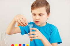 O menino bonito novo é contratado em experiências químicas no laboratório fotografia de stock