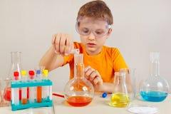 O menino bonito novo em óculos de proteção de segurança é contratado em experiências químicas no laboratório Imagens de Stock Royalty Free