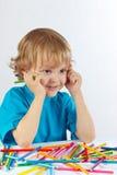 O menino bonito novo na tabela com cor escreve imagens de stock