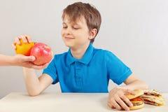O menino bonito novo na tabela escolhe entre o fastfood e a dieta saudável no fundo branco imagem de stock