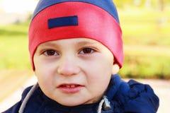 O menino bonito olha à câmera Fotografia de Stock