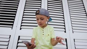 O menino bonito olha as lições video dançar, dançando a escuta a música do telefone nos fones de ouvido O menino do menino filme