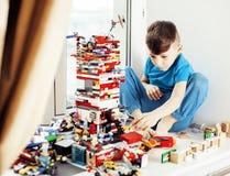 O menino bonito pequeno da criança em idade pré-escolar que joga o lego brinca em casa o sorriso feliz, conceito das crianças do  foto de stock