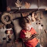 O menino bonito pequeno encontra-se no assoalho de madeira com folhas de outono e l?-se o livro Rapaz pequeno louro que descansa  fotos de stock royalty free