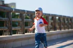 O menino bonito pequeno está andando no porto Fotos de Stock