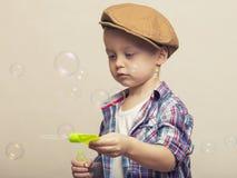 O menino bonito pequeno está fundindo bancos do sabão Foto de Stock