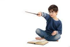 O menino bonito pequeno está lendo um livro e está imaginando-se um herói Imagens de Stock