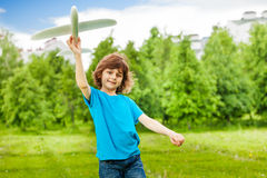 O menino bonito pequeno mantém o brinquedo branco do avião sozinho Fotografia de Stock Royalty Free