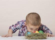 O menino bonito pequeno olha ovos da páscoa coloridos Imagens de Stock
