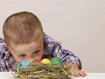 O menino bonito pequeno olha ovos da páscoa coloridos Imagens de Stock Royalty Free