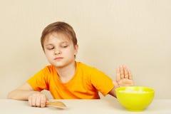 O menino bonito pequeno recusa comer o cereal Imagens de Stock