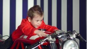 O menino bonito pequeno senta-se na motocicleta vermelha grande O rapaz pequeno sorri no estúdio no estilo americano Feche acima  vídeos de arquivo