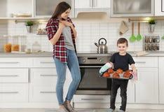 O menino bonito que trata a mãe com o forno cozeu bolos imagens de stock royalty free