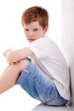 O menino bonito, sentando-se no assoalho cansou-se imagens de stock royalty free