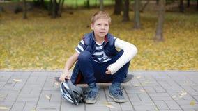O menino branco com braço quebrado pôs de seu capacete vídeos de arquivo