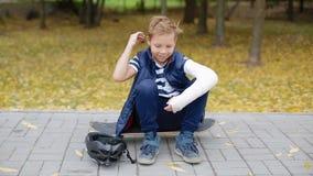 O menino branco com braço quebrado pôs sobre seu capacete vídeos de arquivo