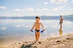 O menino bronzeado de três anos em troncos de natação joga no lago no verão, férias de verão foto de stock royalty free