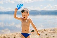 O menino bronzeado de três anos em troncos de natação joga no lago no verão, infância imagem de stock royalty free
