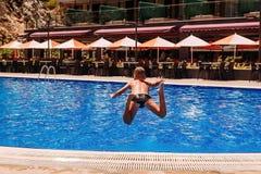 O menino bronzeado salta com uma corrida na associação exterior do verão, vista traseira imagem de stock