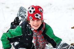 O menino cai na neve imagens de stock