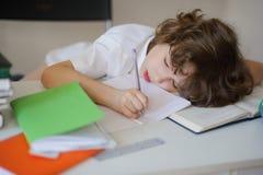 O menino cai trabalhos de casa fazendo adormecidos Fotos de Stock Royalty Free