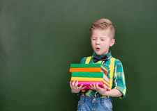 O menino cansado com uma pilha de livros pesados aproxima o quadro verde vazio Foto de Stock