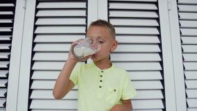 O menino caucasiano novo está bebendo um vidro do leite branco O menino bonito no t-shirt está bebendo um vidro do leite fresco n vídeos de arquivo